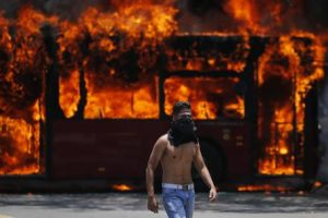 An anti-government protester walks near a bus that was set on fire by opponents of Venezuela's President Nicolas Maduro during clashes between rebel and loyalist soldiers in Caracas, Venezuela, Tuesday, April 30, 2019. Venezuelan opposition leader Juan Guaidó took to the streets with a small contingent of heavily armed troops early Tuesday in a bold and risky call for the military to rise up and oust Maduro. (ANSA/AP Photo/Fernando Llano) [CopyrightNotice: Copyright 2019 The Associated Press. All rights reserved]